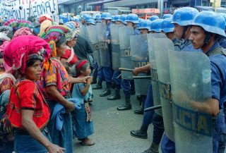 Clash of Two Worlds, 1492-1992. A Group of campesinos from Cajolá plantation are confronted by the National Police in downtown Guatemala City. The campesinos had come to the city to demanding land to work and live in. 21/07/92
