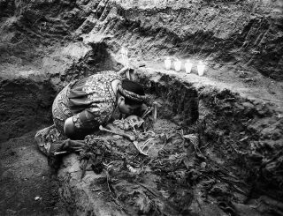 Rigoberta Menchu Tum kisses the remains of a person killed during the armed conflict found in a clandestine grave. This was the first time Menchu attended an exhumation. Xiquín Sanahí, Comalapa, Guatemala. March 5,2002.