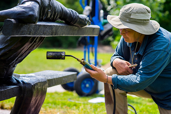 Jo DeDecker blasts a bronze sculpture with heat at the Benson Sculpture Garden in Loveland on July 28, 2016. The bronze sculptures must be heated to soften the existing wax and allow for application of a new wax layer that will keep the artwork clean.  Photo by Michael Ortiz/Loveland Reporter-Herald
